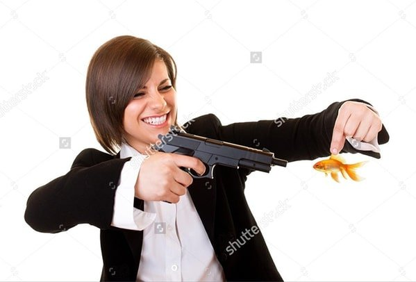 WTF stock photos woman with gun held up against a fish