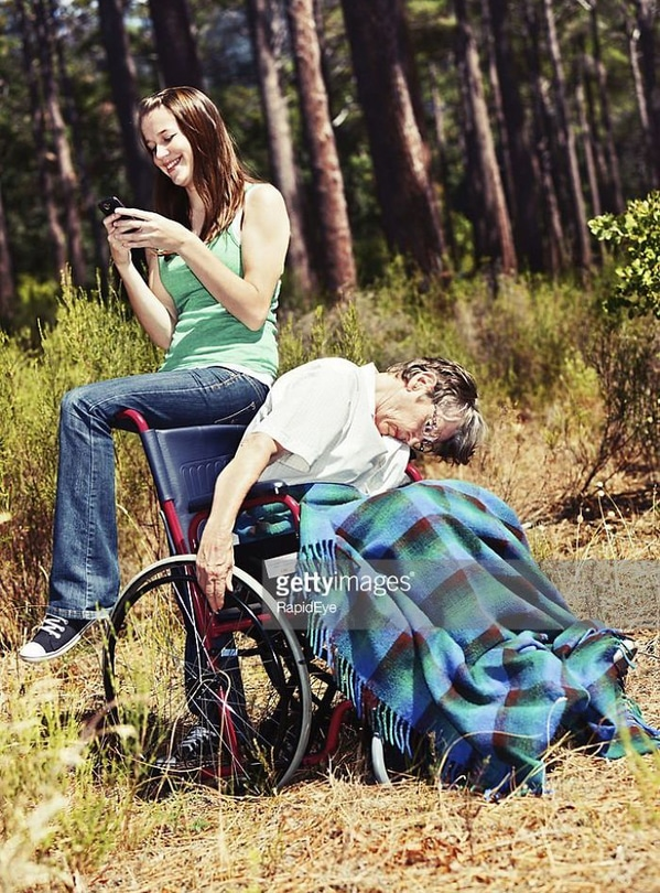 WTF stock photos dead man in a wheelchair while young woman texts