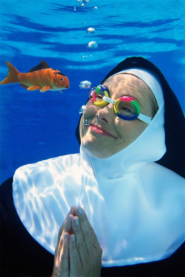 nun in goggles underwater and looking at a goldfish