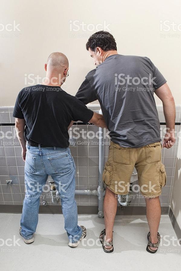 man helping another man pee WTF stock photos