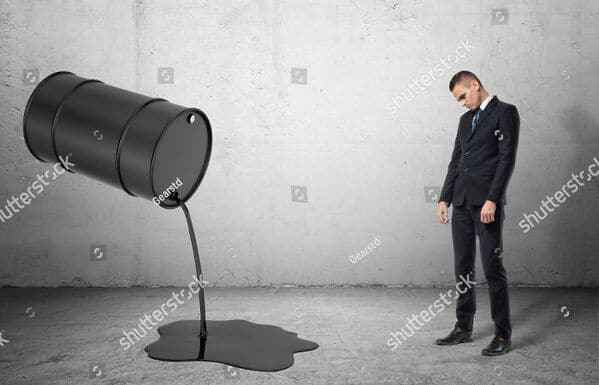 WTF stock photos oil dripping from barrel man looks on