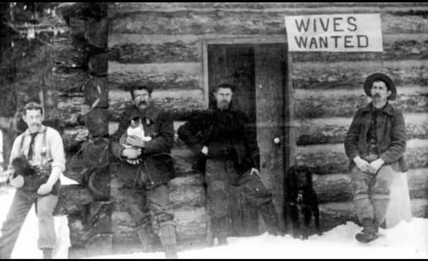 black and white photo of men outside a log cabin with a sign that says wives wanted, Funny Fake history photos, r fakehistoryporn, facts about history that are not true, false textbook photos, historical pics with funny captions, lol, jokes, old photos with hilarious explanations, funny pics